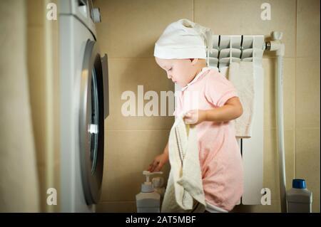 La niña se encuentra frente a una lavadora con una toalla en la mano. Primer plano
