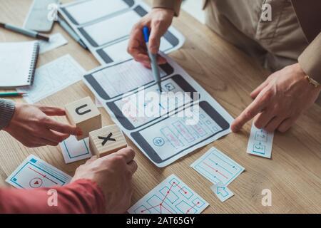 Vista recortada de diseñadores con bocetos y cubos de estructura alámbrica de sitio web móvil con letras ux en la tabla