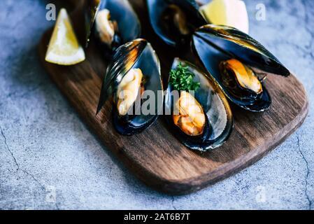 Mejillones cocidos con hierbas de fondo limón y plato oscuro / mariscos frescos en tabla de cortar de madera en el restaurante mejillón de mariscos