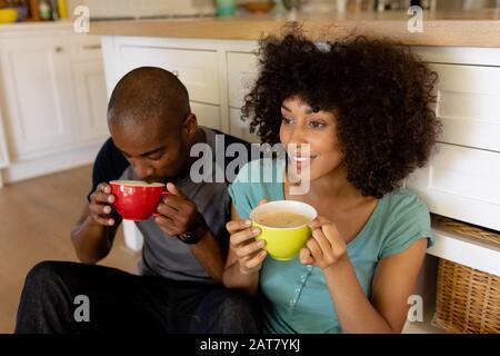 Feliz pareja joven sentado en la cocina Foto de stock