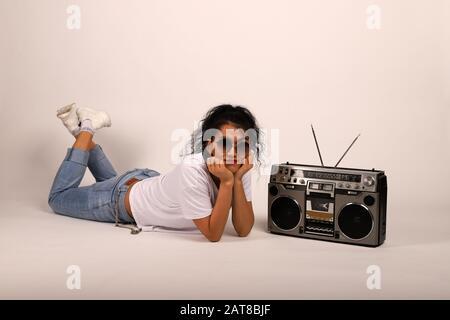 Feliz chica en una camiseta blanca y jeans miente y escucha música. Reproductor de cinta retro y chica. El estilo hip-hop es una joven a la que le encanta la música Foto de stock
