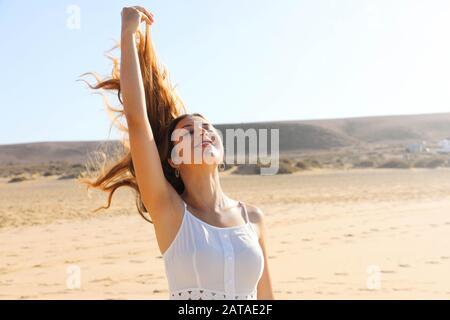 Mujer sin preocupaciones respirando aire fresco en la playa con pelo volador en el viento