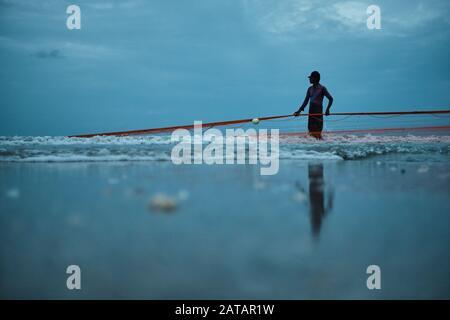 Pescador sacando las redes del océano en la playa en Sri Lanka. La ciudad de Trincomalee tiene una gran y larga playa donde los lugareños tiran de redes y peces.