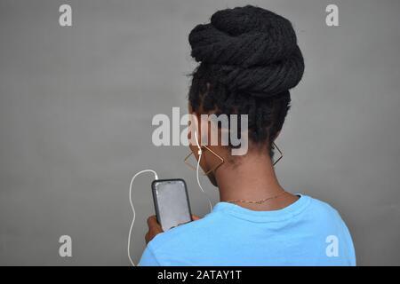 joven mujer negra con peinado africano escuchando música, vista posterior