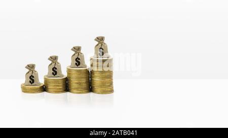 Concepto de banner de inversión y ahorro de dinero. Bolsa de dinero en alza apilada de monedas sobre fondo blanco y espacio. Demostrar riqueza duradera a largo plazo
