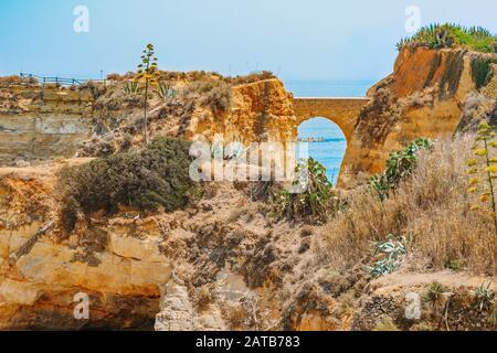 Playa de estudiantes en Algarve, Portugal. Mar y acantilados sobre el fondo. Puente romano que conecta los acantilados sobre la playa. Paisaje paisaje