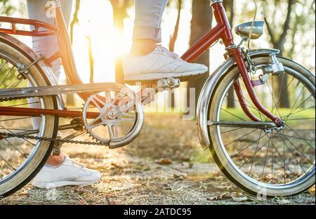 Mujer joven en bicicleta italiana de estilo antiguo con Back light - Cerca de chica montando bicicleta vintage de pies en el parque al aire libre tiempo de caída de la moda Vintage - c