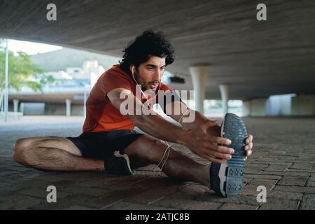 Joven corredor masculino escuchando música en el auricular estirando las piernas antes de correr y hacer ejercicio en la calle bajo el puente