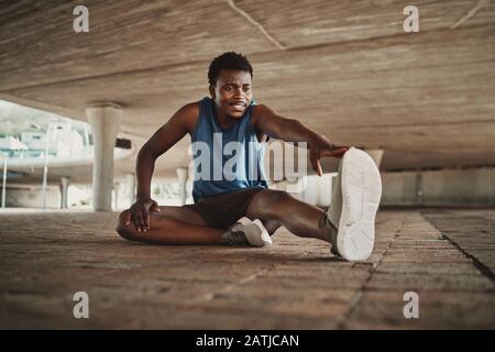 Retrato sonriente de un joven estirando sus brazos y piernas mientras se sienta en el pavimento bajo el puente