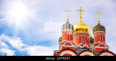 Iglesia ortodoxa contra el cielo azul con nubes y sol. Religión en Rusia concepto, bandera