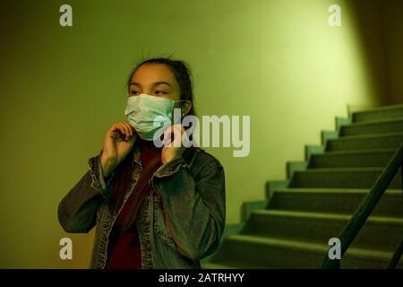 Retrato de una joven asiática. Escalera del hospital. La niña lleva una máscara para evitar infectarse con el virus
