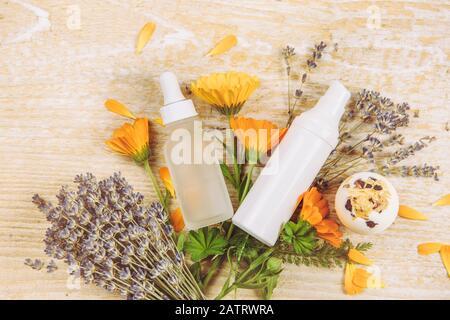 Concepto de cosméticos orgánicos basados en plantas. Vista superior de varias plantas de hierbas y envases de productos de belleza sobre fondo de madera texturizada, mucho espacio de copia.