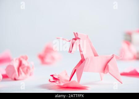 Unicornio de origami rosa con bolas de papel arrugadas. El proceso creativo es la escritura, el fondo ligero