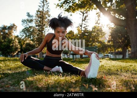 Retrato de una determinada mujer afroamericana sentada en hierba verde haciendo ejercicio en el parque - joven mujer negra calentándola