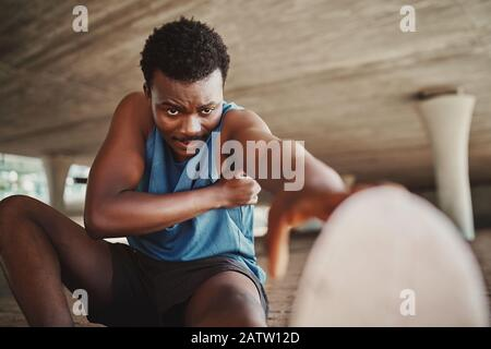 Retrato de un corredor masculino tratando de estirar las piernas antes de correr al aire libre