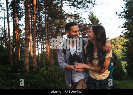 La pareja feliz está haciendo senderismo en el bosque por la tarde. Foto de stock