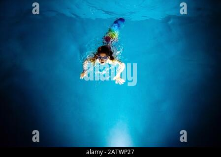 Buceo de sirena hacia la luz de una piscina azul en la noche, con un fondo de ensueño de la fantasía y la imaginación.