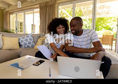 Feliz pareja joven discutiendo en el sofá Foto de stock