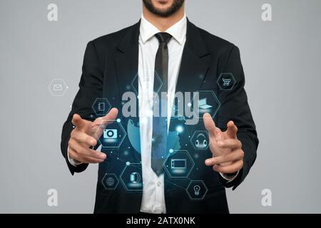 Vista frontal de incógnito empresario en traje negro en la oficina. El hombre sostiene la proyección virtual en 3D de las cartas táctiles digitales en los brazos. Concepto de alta tecnología, digitalización.