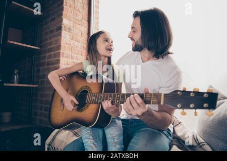 Foto de la pequeña adorable dama bonita y su guapo joven papá sentarse ventana bajo los ojos mantener la guitarra acústica aprender nueva canción pasar tiempo