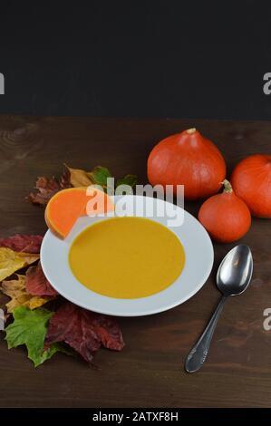 sopa de calabaza otoñal en un bol con calabazas hokkaido, hojas y una cuchara en una mesa de madera marrón