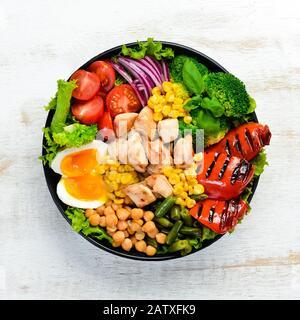 Cuenco de Buda: Pollo, garbanzos, garbanzos, brócoli, tomates, huevos, pimentón, cebolla en un plato negro sobre un fondo de madera blanco. Vista superior. Espacio libre Foto de stock