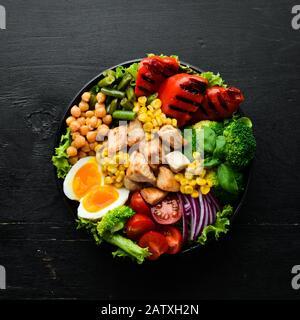 Buddha Bowl: Pollo, garbanzos, brócoli, tomates, huevo, pimentón, cebolla en un plato negro sobre fondo negro. Vista superior. Espacio libre para el texto. Foto de stock