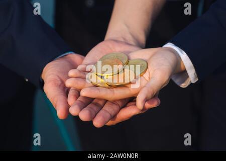 Joven empresario asiático holding bitcoin dorado en frente de su equipo multiétnico internacional en la ciudad moderna.