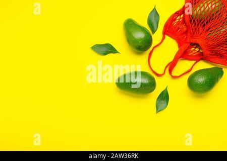 Frutos de aguacates en bolsa ecológica de malla roja reutilizable. Bolsa de malla reciclada para frutas o verduras. Sin plástico, concepto de compras sin residuos. Mínima capa plana