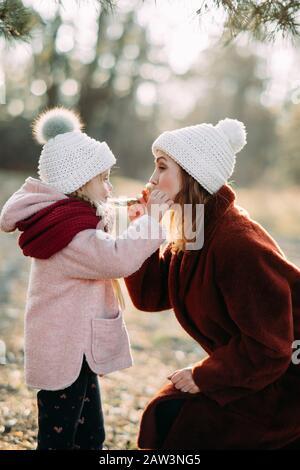 La madre y la hija juegan y se divierten mientras caminan por el bosque.