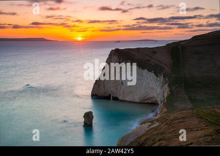 Lulworth, Dorset, Reino Unido. 6 de febrero de 2020. Clima en el Reino Unido. Una dorada puesta de sol en Bats Head cerca de Lulworth en Dorset mirando al oeste hacia Weymouth y la isla de Portland vista desde el camino de la costa suroeste en Swyre Head. Crédito De La Imagen: Graham Hunt/Alamy Live News Foto de stock