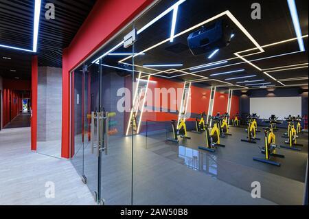 Aeróbic haciendo girar bicicletas en el gimnasio detrás de una puerta de vidrio Foto de stock