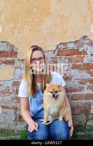 Joven, linda chica de al lado con gafas rojas, jeans y camiseta, posando con su mascota frente a la pared de ladrillo grunge