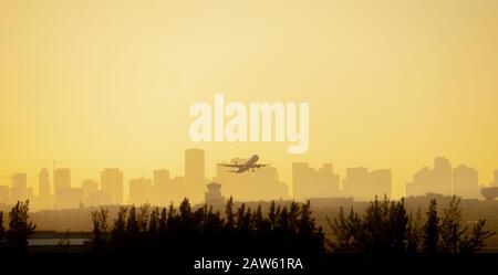 Un avión se perfila frente a un colorido amanecer amarillo y naranja, ya que sale del aeropuerto de Miami con la ciudad en el fondo.