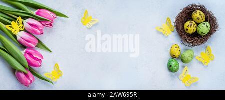 Banner De Pascua De Fondo. Huevos de Pascua en Nest y tulipanes rosas en la mesa de piedra azul de fondo. Concepto De Vacaciones De Primavera. Vista superior, espacio de copia, plano