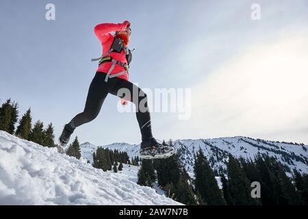 Mujer corredor de pista corriendo en las montañas de invierno en la nieve. Dinámica cuesta abajo en la vista lateral de la corredora de atletismo
