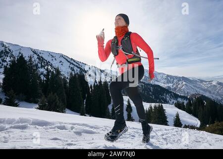 Mujer corredor de pista corriendo en las montañas de invierno en la nieve. Carrera dinámica cuesta arriba en la vista lateral de la atleta de la mujer trail