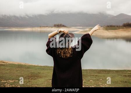 Mujer turística explorando el lago. Ella está de pie girada hacia atrás y mirando a distancia, con sus manos en el aire.