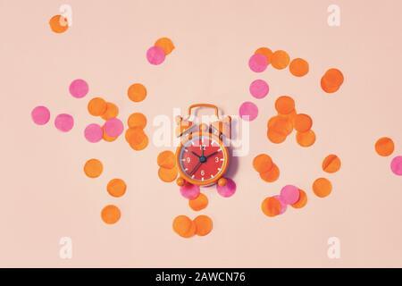 El reloj de alarma vintage muestra 10 horas y 10 minutos entre los confeti multicolores como concepto para celebrar la vista superior de fondo festivo