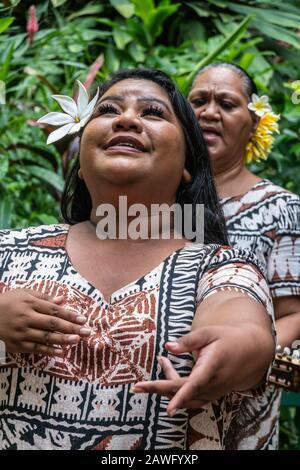 Kamokila Village, Kauai, Hawaii, Estados Unidos. - 16 de enero de 2020: La cantante folclórica femenina interpreta una canción de boda en el escenario frente a Fern Grotto. Fondo verde.