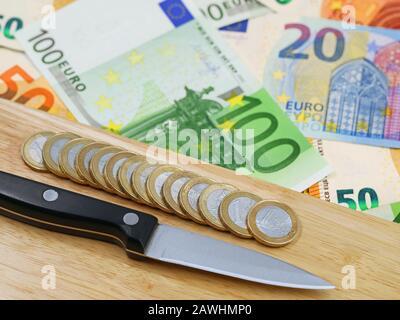monedas de un euro en el tablero de madera con el fondo del cuchillo y del billete del euro
