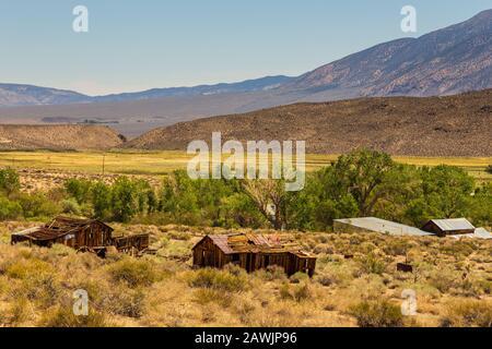 Antiguos edificios de madera junto a fuentes termales. Montañas nevadas de Sierra Nevada en el fondo, Benton, California, Estados Unidos.