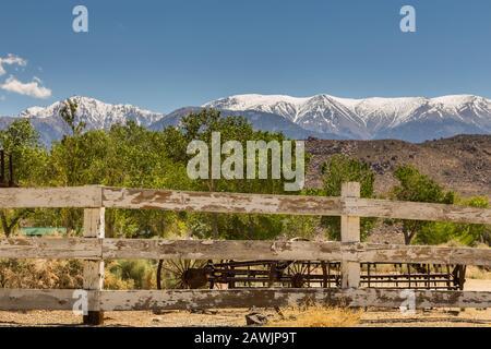Maquinaria agrícola antigua detrás de la cerca.nevadas Sierra Nevada montañas en el fondo, Benton, California, EE.UU..