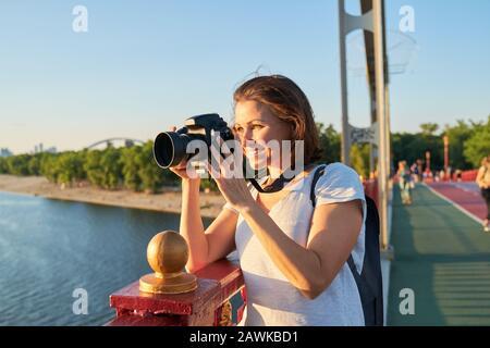 Mujer adulta fotógrafa con cámara fotográfica