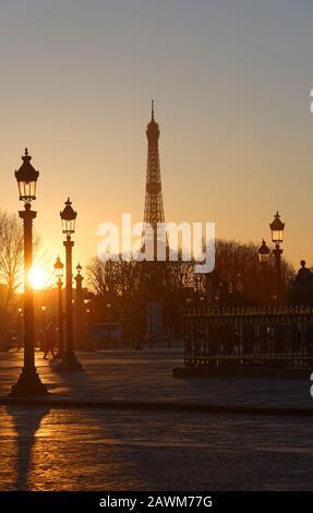 Siluetas de la Torre Eiffel, lámparas callejeras de la Plaza de la Concordia al atardecer en París.