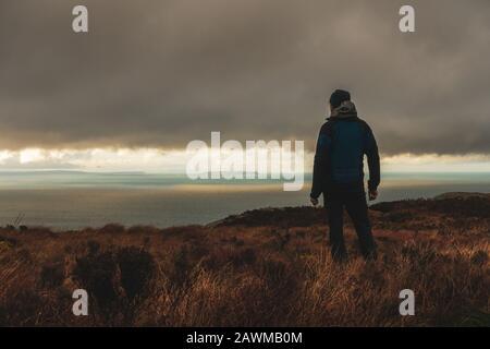Persona admirando las vistas desde el Mull of Kintyre a Irlanda del Norte y la isla Rathlin en condiciones meteorológicas dramáticas en invierno, Escocia, Reino Unido