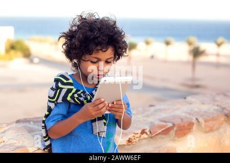 Niño jugando juegos en la tableta al aire libre. Los niños, la tecnología y el concepto de adicción a los gadgets