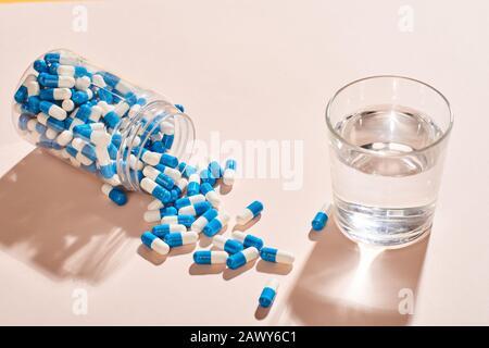 Cápsulas blancas Y azules derramadas de botella caída y vidrio de agua sobre superficie de mesa rosa pálido, inyección horizontal