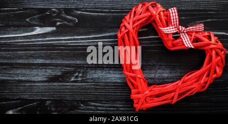 Corazón rojo hecho a mano sobre tablero de madera negro. Tarjeta de regalo romántica en estilo vintage, patrón con copia, espacio de texto. Día de San Valentín fondo. Símbolo de la lov