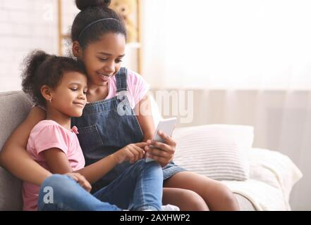 Niña afroamericana jugando en el celular de su hermana